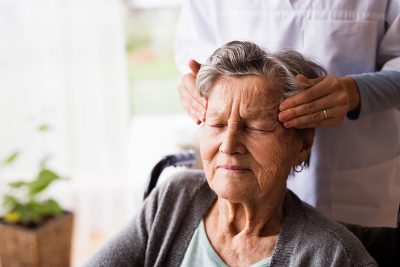 alzheimer's treatment, Health visitor and a senior woman during home visit. Unrecognizable nurse giving woman temple massage.