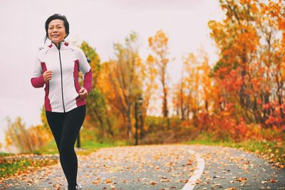 retirement hobbies; Mature Asian woman running active in her 50s. Middle aged female jogging outdoor living healthy lifestyle in beautiful autumn city park in colorful fall foliage. Asian Chinese adult in her fifties.