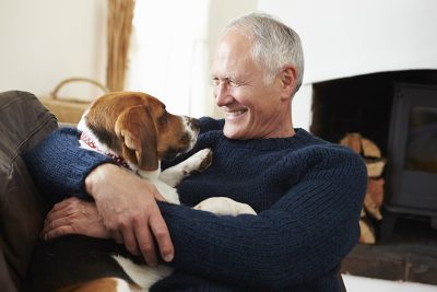 Senior Man Relaxing At Home With Pet Dog; pets; health benefits; companionship; retirement