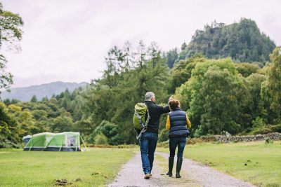 Senior couple are enjoying a scenic walk through the woodlands at the Lake District.