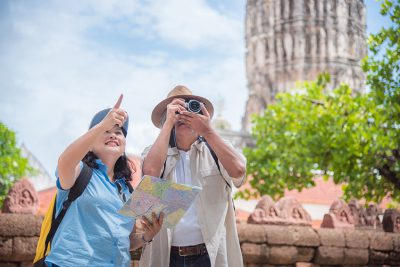 Retired asian couple traveling at temple in Thailand.