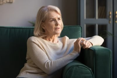 Upset thoughtful grey haired mature woman feeling worried about problems, frustrated middle aged female looking away, thinking of loneliness, pensive depressed senior female sitting on couch alone; phobia