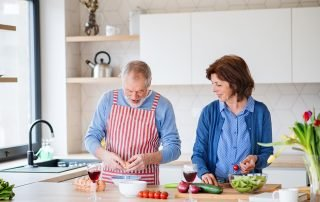 A portrait of happy senior couple indoors at home, cooking.